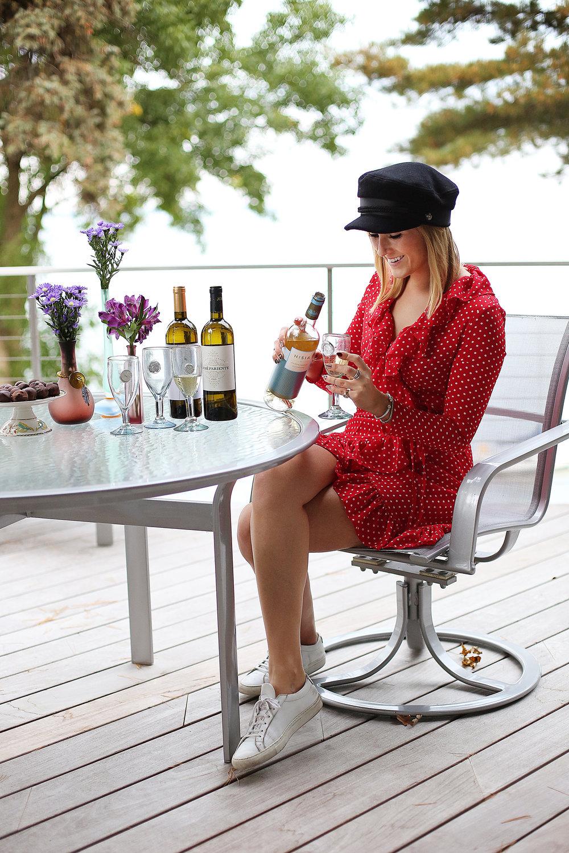 blonde girl drinking wine red dress black hat