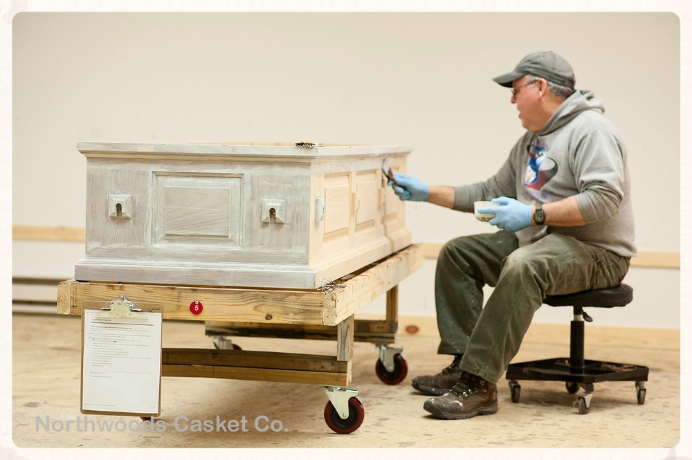 Jeff applying a white milk paint glaze finish to a raised panel oak casket shell.