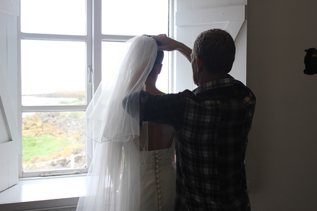 Stylist Carl securing a veil in place on our beautiful model Lowri who is wearing our Nadia gown.