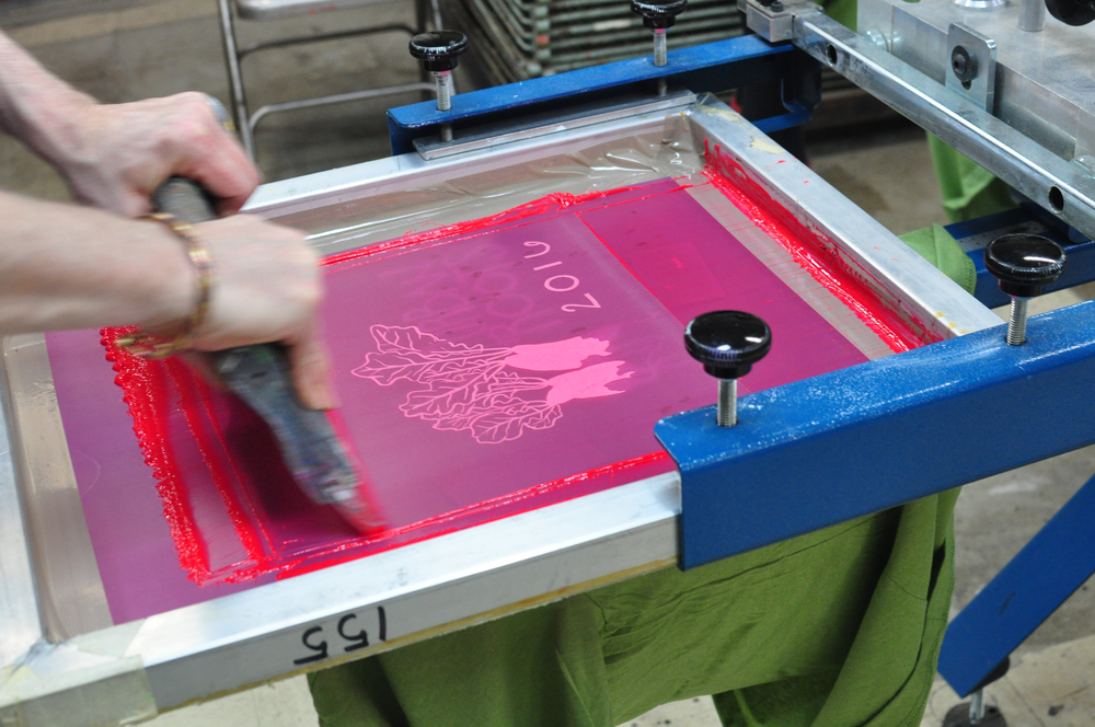 printing the magenta layer on a 2-color t-shirt. did you know we print everything by hand?
