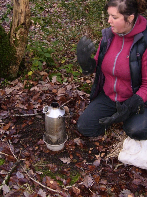 TEA TIME. Note the kneeling position (as modeled by Lily), cork out, established zones with sticks, thermal gloves and flat surface. If you see someone using a storm kettle without this then challenge them - They're not safe and could scold someone!