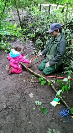 Children learn safety rules and to assess risks. Here a child is learning to use a tool safely to help make a hazel hurdle.