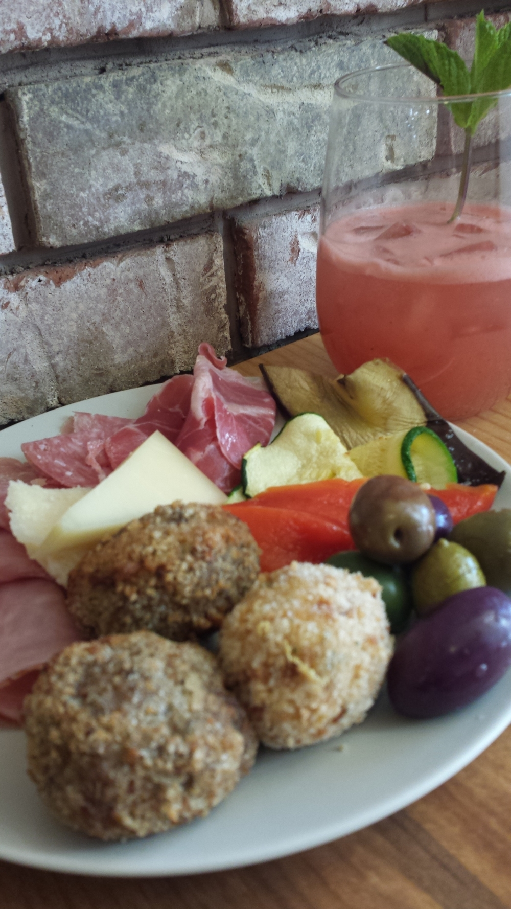 Prococco cocktail, meatless meatballs, olivi misti, affetatti, and roasted vegetables for a perfect pick-me-up after work.