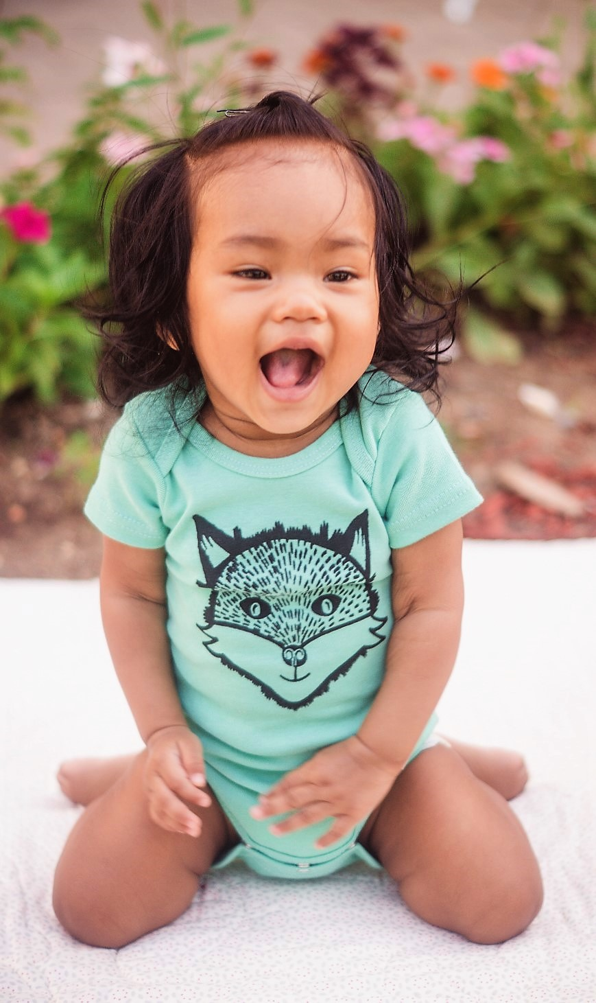"Yinibini Baby model wearing 'Clever Like a Fox"" One-Piece in Seafoam."