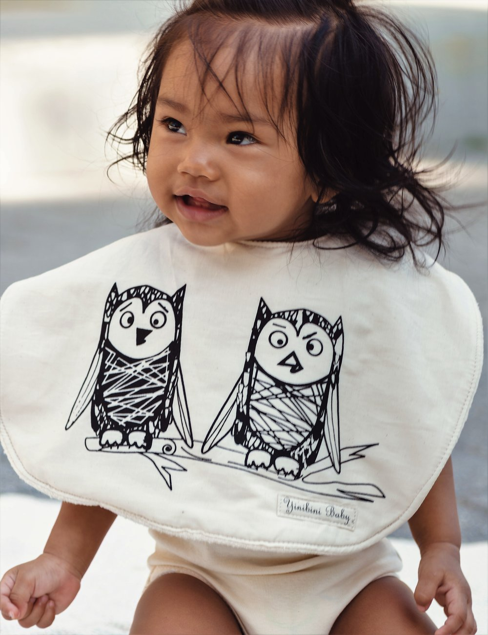 Yinibini Baby model wearing the Owlets Reversible Organic Cotton Bib in Natural