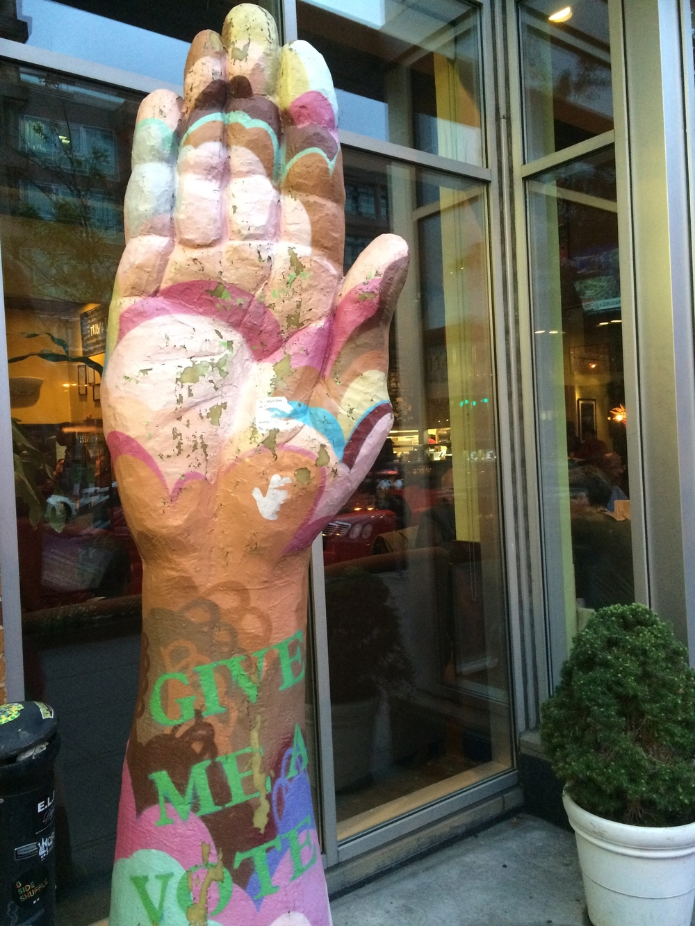 "learn about the ""give me a vote"" hand sculptures"