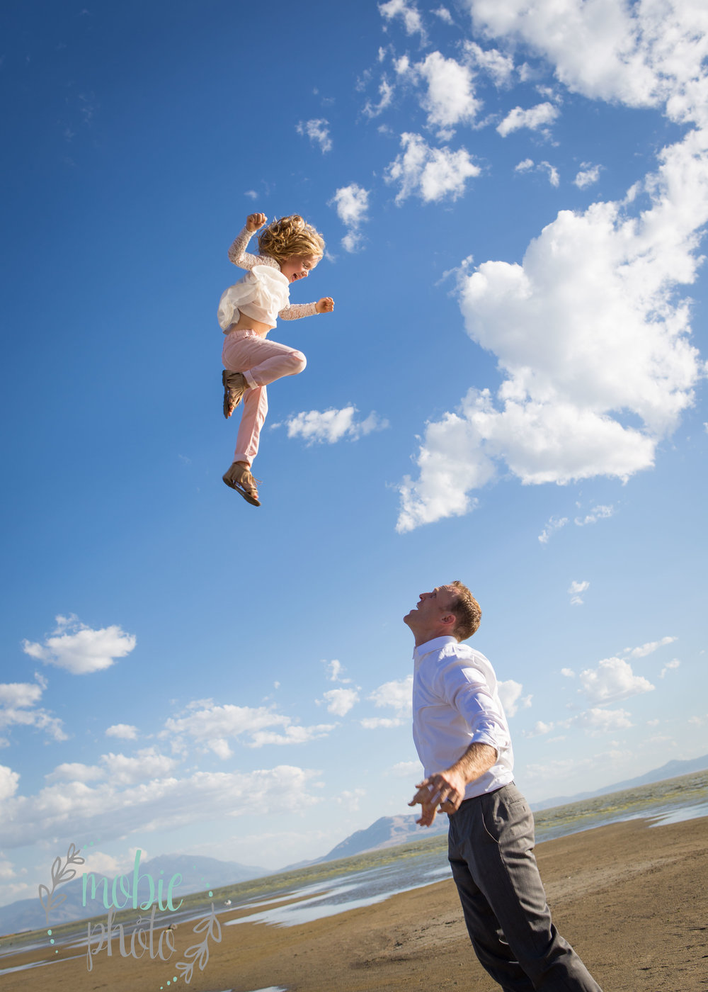 Dad throwing his daughter in the air