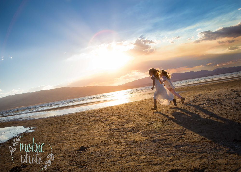 Sisters running on the beach at sunset - Utah Lake