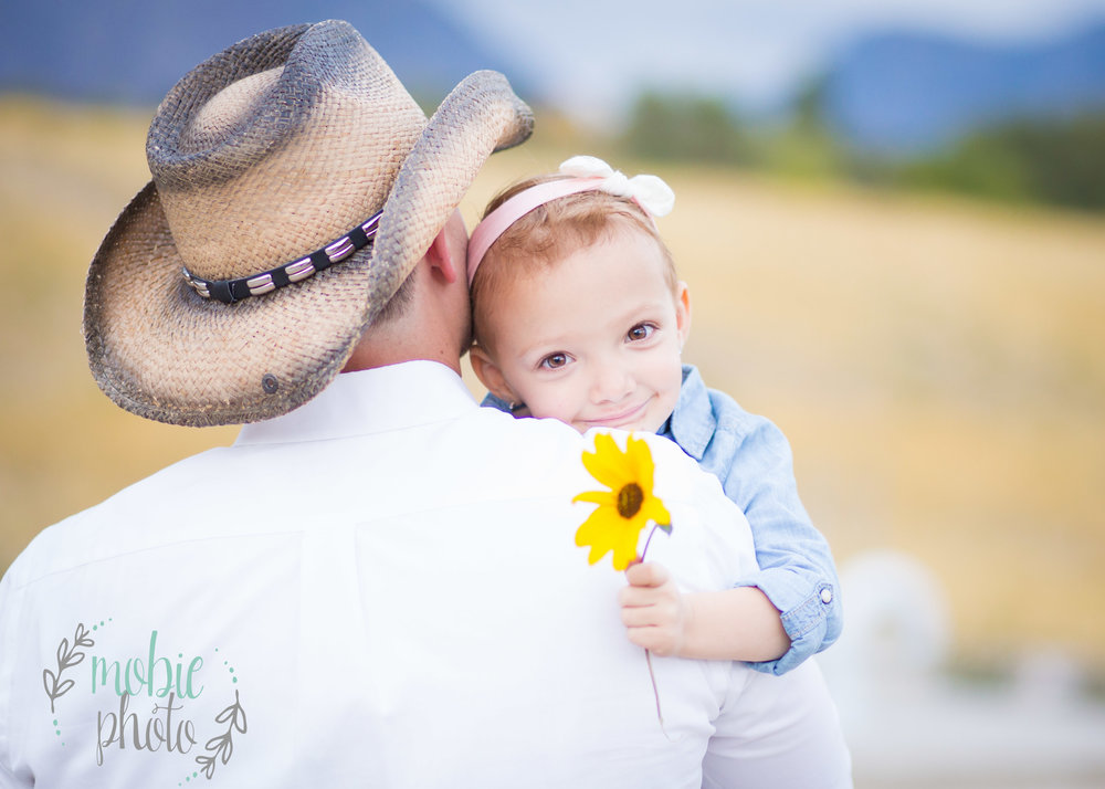 Little girl hugging cowboy daddy