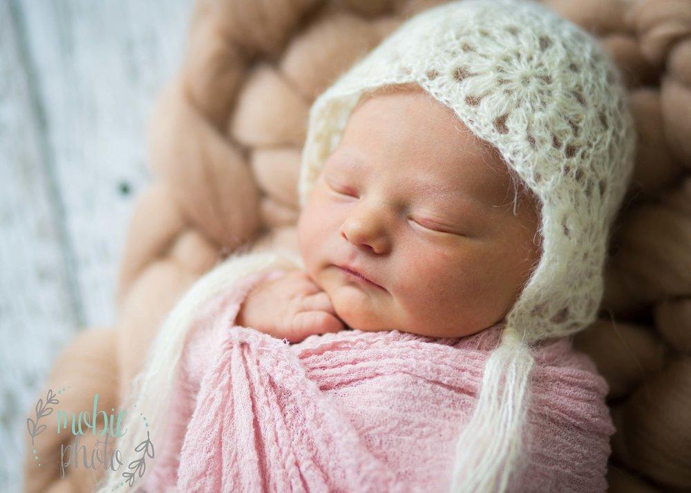 Newborn girl in white bonnet