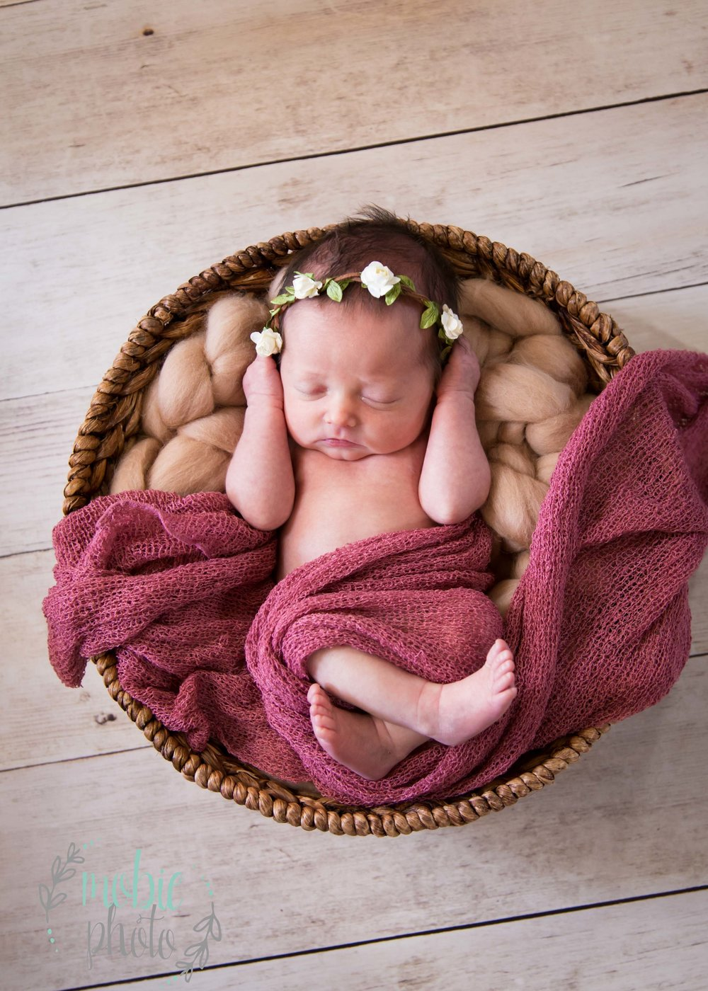 Newborn Girl in Round Basket with Pink Wrap and Flower Headband
