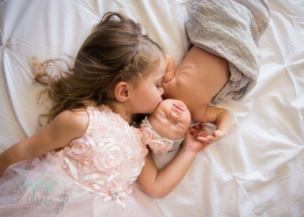 Two year old kissing her baby sister - pink and white and gray color scheme
