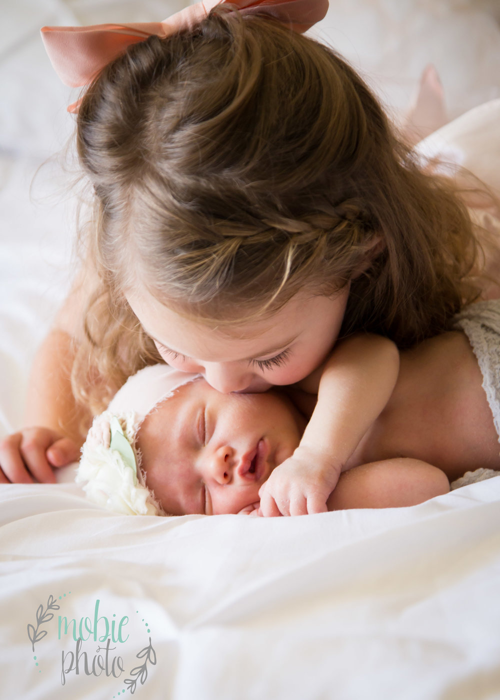 Two year old kissing her newborn sister