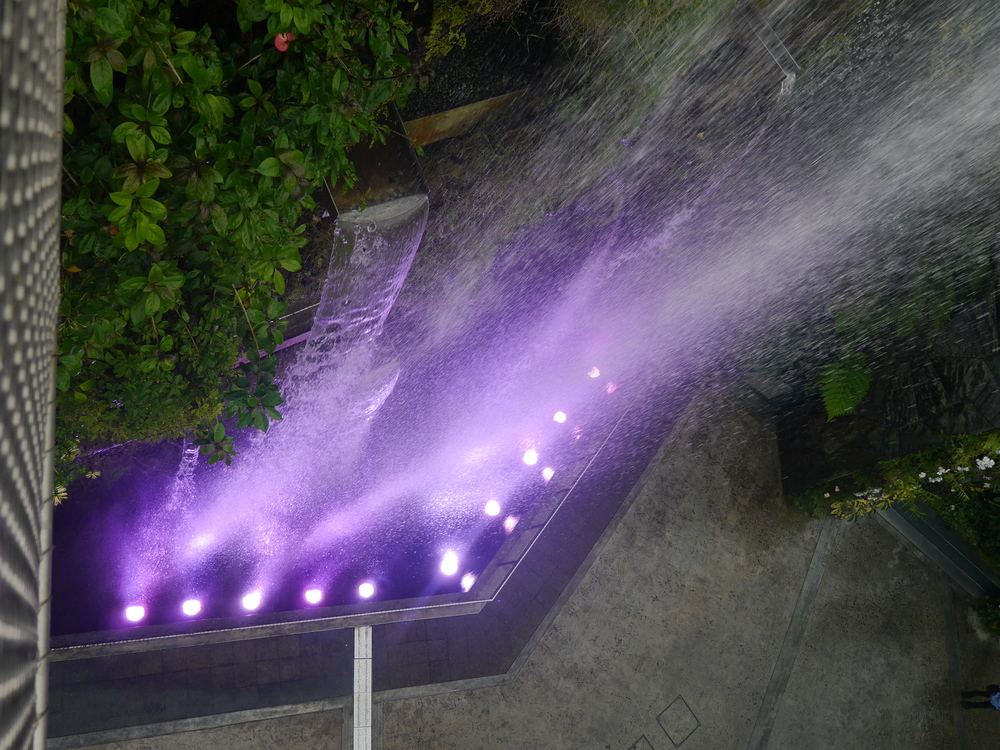 The waterfall is lit from below at night.