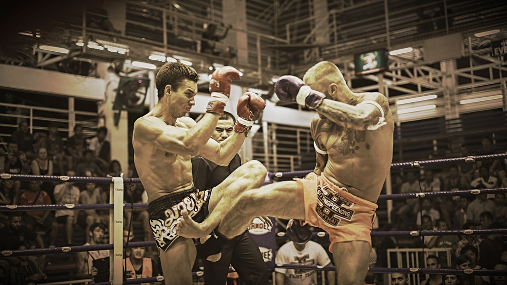 Head Muay Thai instructor Kris Barras fighting in Thailand (orange shorts)