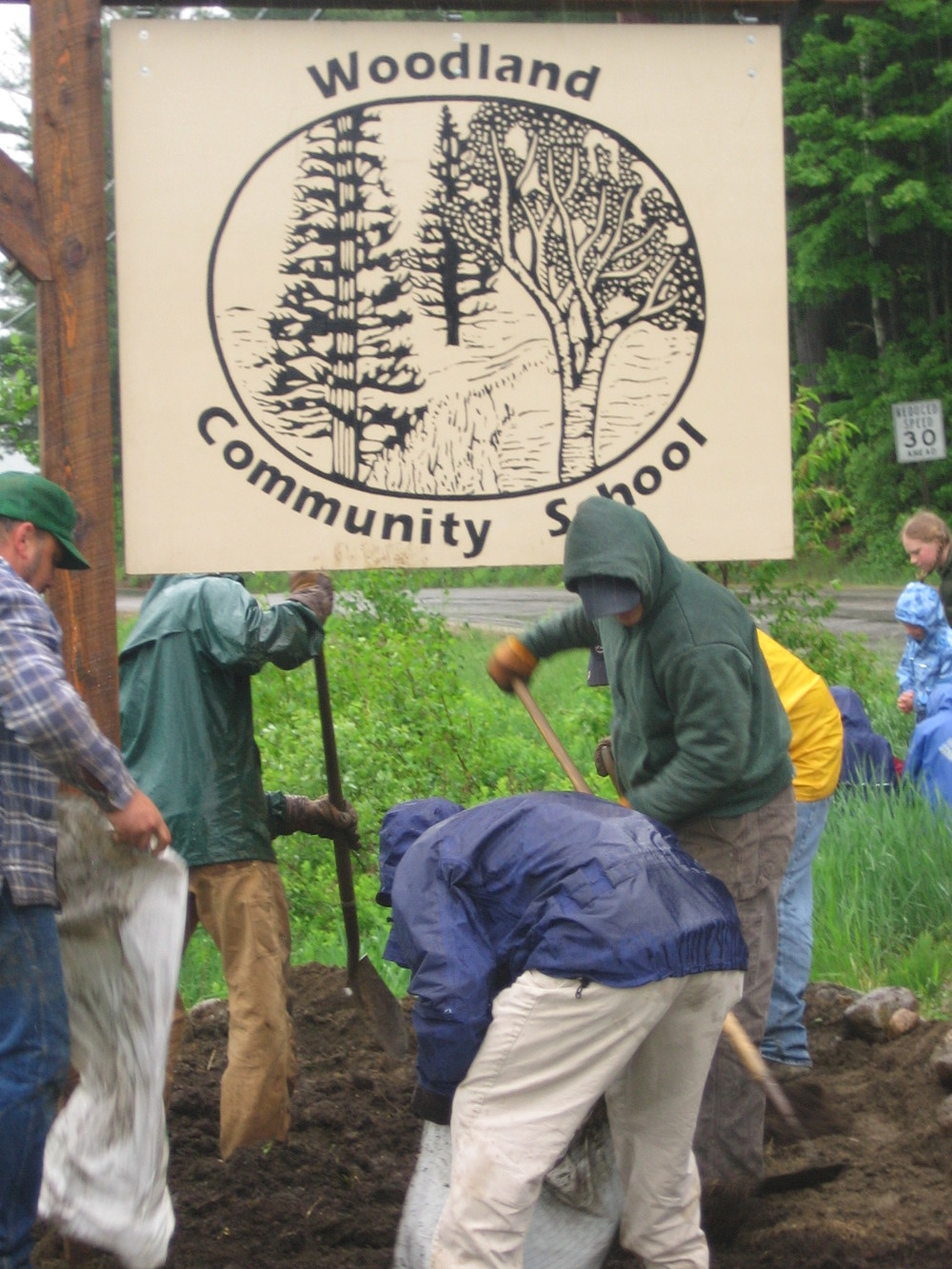 Woodland Parents and Board Members work together to make a flower bed for our Woodland Community School  Sign