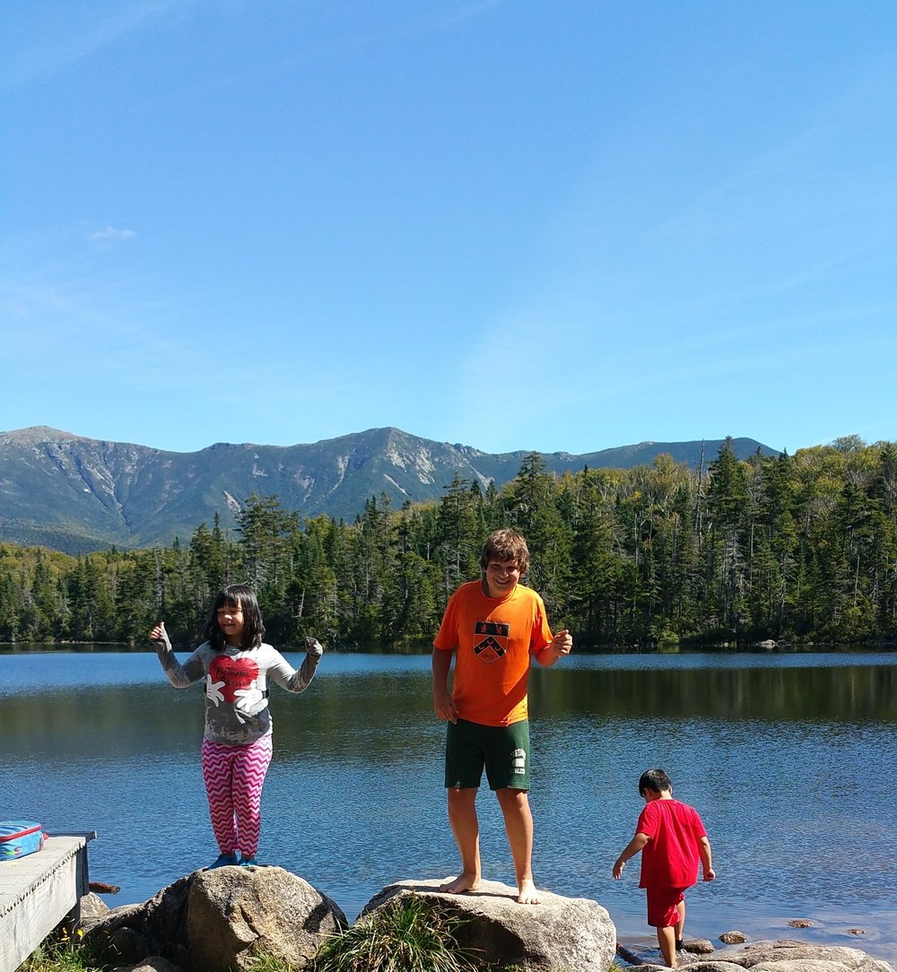 "Inspired by the beauty of Lonesome Lake and the surrounding mountains, Nina and Cole belt out an original song!   woodland commmunity school once again took to the trails as we hiked to lonesome lake. it was a gorgeous day for a hike with many interesting geographic features and critters to notice along the way. once we reached the lake many students opted to go for a swim or wade in the cool, clear water.  students burst into spontaneous song with zoe and cole leading the group singing in ""rounds."""