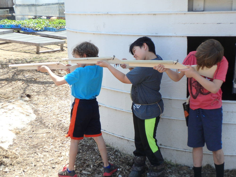 - After sanding and sanding and more sanding, this group of students took their rifles out for a spin on the farm! It took a few days of hard work and attention to detail to turn out these Wild West rifles. After all the hard work, this group of boys also worked equally hard at pitching in to clean up the woodworking porch, drag things to the farm burn pile, and make sure tools were properly put back in their places.