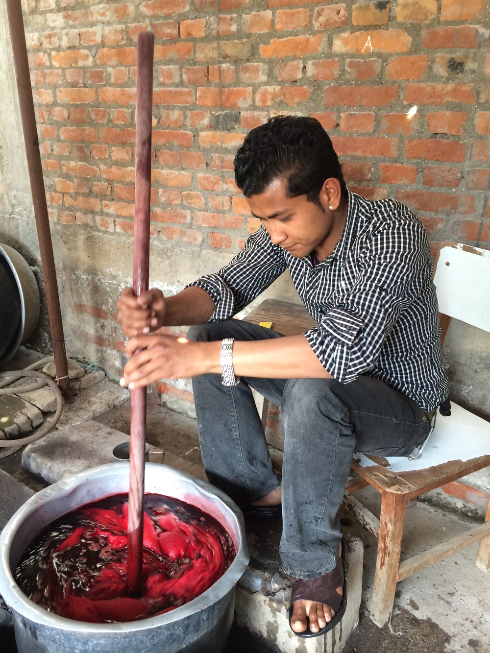 Stirring a throw in the dye bath.