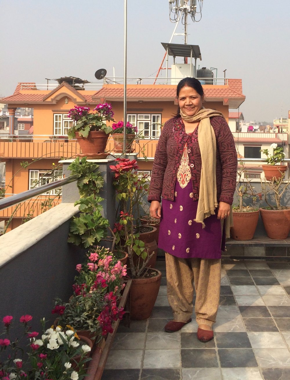 Tika on the rooftop surrounded by her beloved flower garden