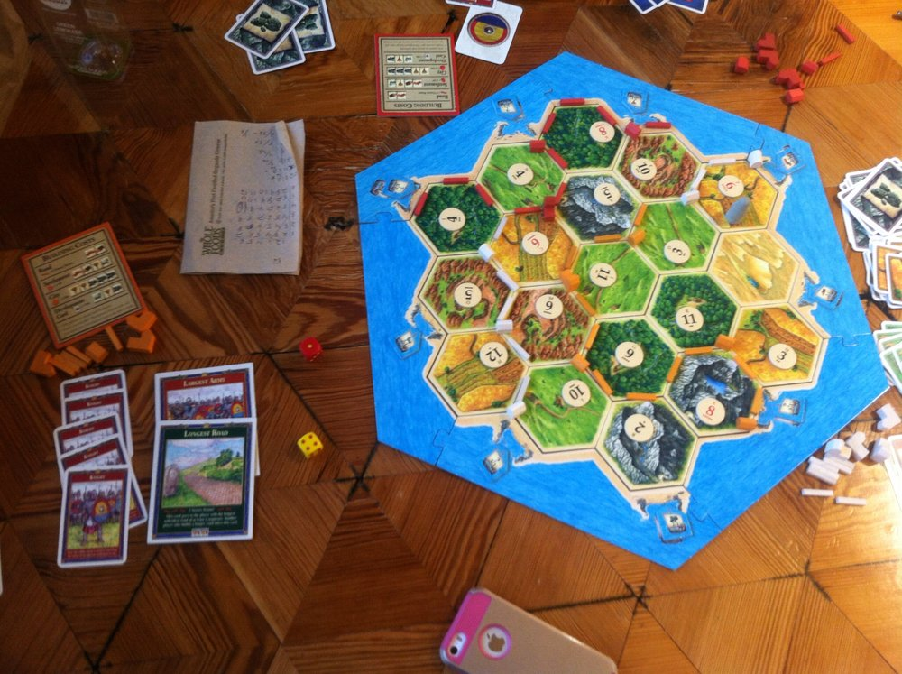 The final board of the second game. I (orange) won by building four settlements, a city, the longest road, and the largest army.