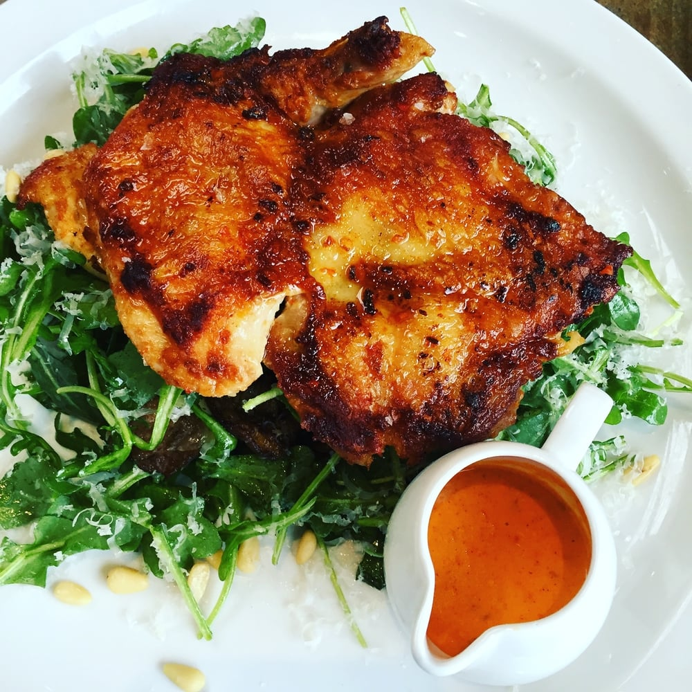 Roasted Hen with Piri Piri and a bed of tossed arugula salad.
