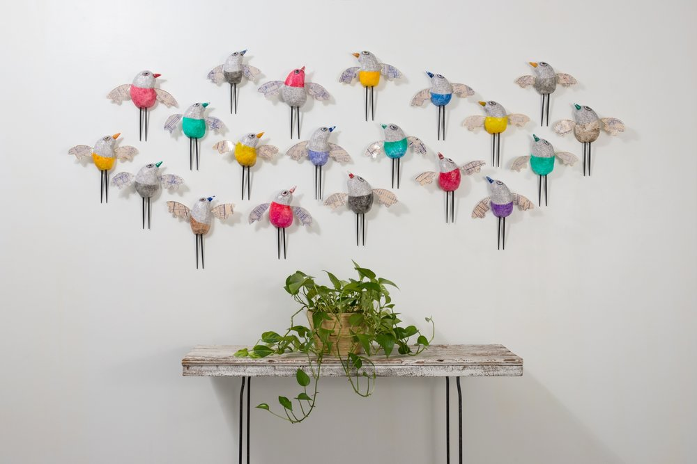The Bird House Collection features twenty individual artworks united by authentic architectural blueprints for wings and vintage tree light glass bulbs as beaks.