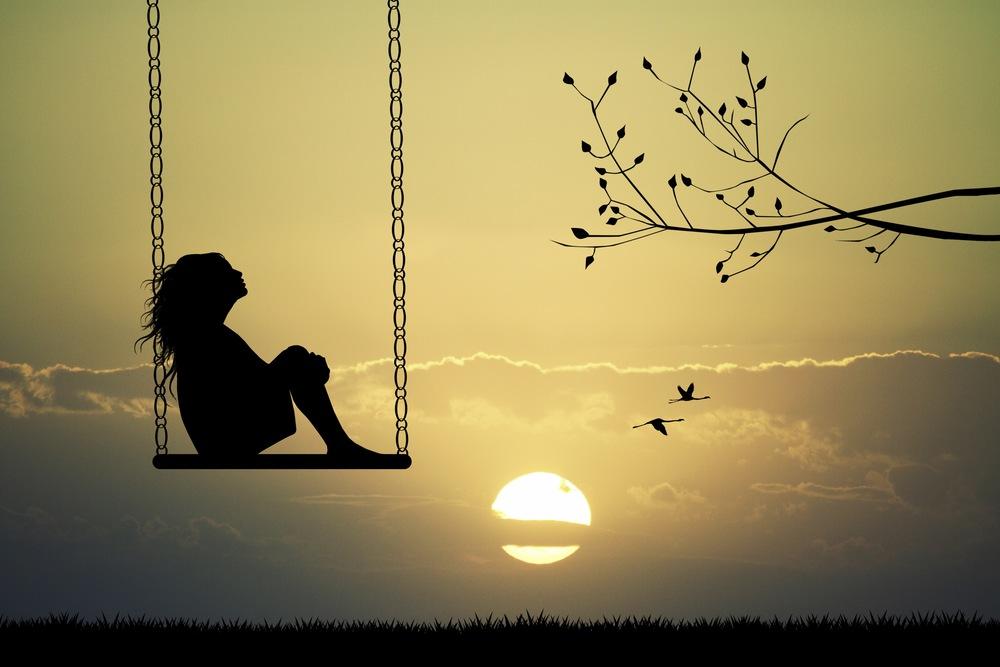 Girl on swing at sunset