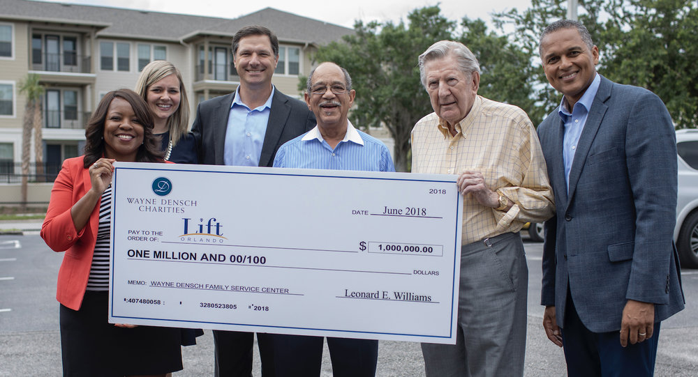 Wayne Densch Charities presents the check to LIFT representatives at the LIFT Orlando HUB. In the background is the $40 million mixed-income housing development, Pendana at West Lakes.   From Left to Right: Sherry Paramore, Director of Advancement, LIFT Orlando,Natalie Lovero, Community Partnerships, LIFT Orlando,Steve Hogan, CEO, Florida Citrus Sports Kran Riley, Wayne Densch Charities,Leonard E. Williams Sr., President, Wayne Densch Charities,Eddy Moratin, Executive Director, LIFT Orlando