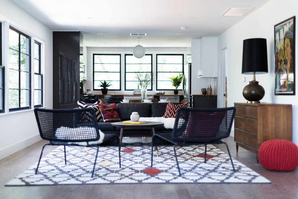 West Elm's  Layla rug  was our first purchase -- and the room's color inspiration. Its Moroccan tile pattern and random red-orange accents gave us permission to go bold with CB2's bright pouf - and some richly toned kilim pillows from Etsy.