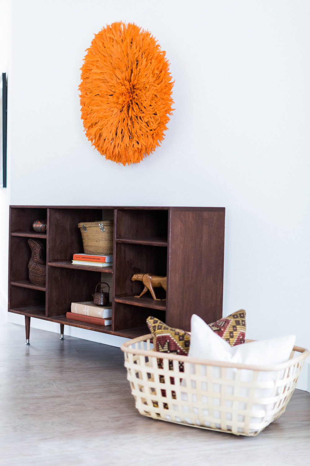 At the entry, this bookcase from LA's Moti Roma holds treasures. And nothing says welcome like a Cameroonian juju feather headdress in shocking orange. We even love IKEA's Viktigt basket to hold more kilim-y goodness.