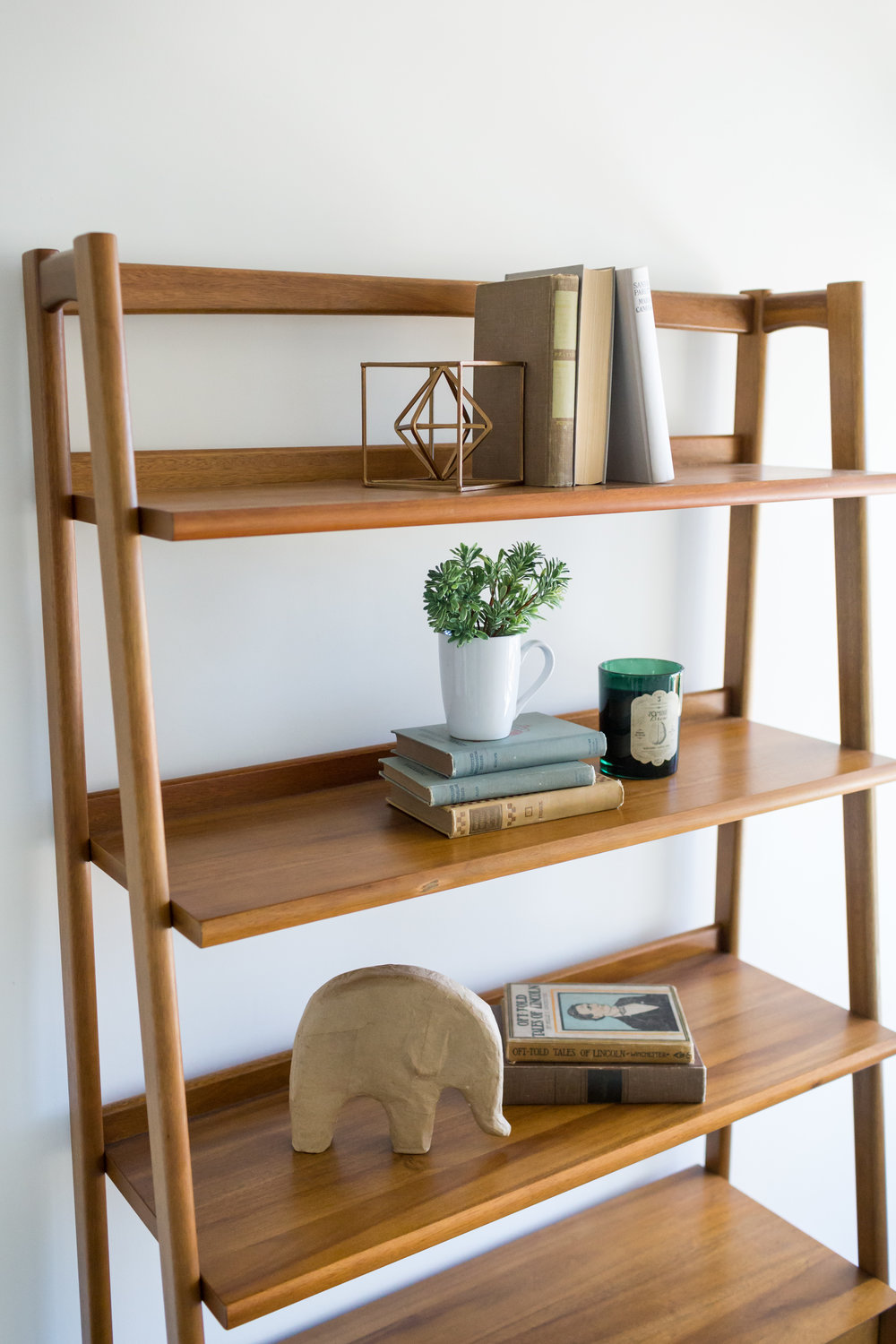 Neutral, modern shapes and vintage books fill out the shelves.