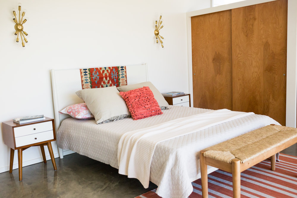 Salmon tones in a second bedroom. A vintage kilim rug found in Paris serves to brighten a wooden headboard.