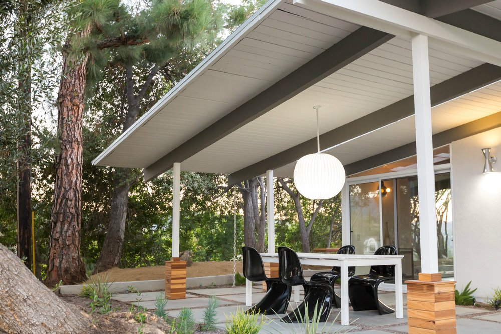 To play up the inherent drama in the outside patio's pendant light, we added the dark and light contrast of black Panton chairs around a white picnic table.