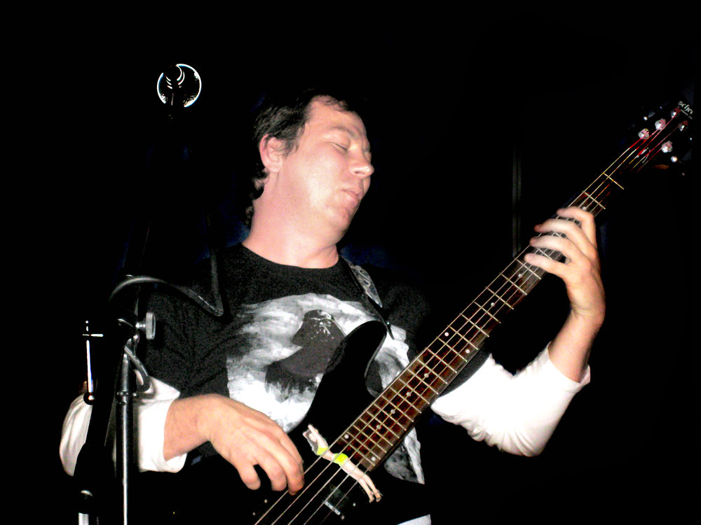 rockbadger plays bass guitar in a band