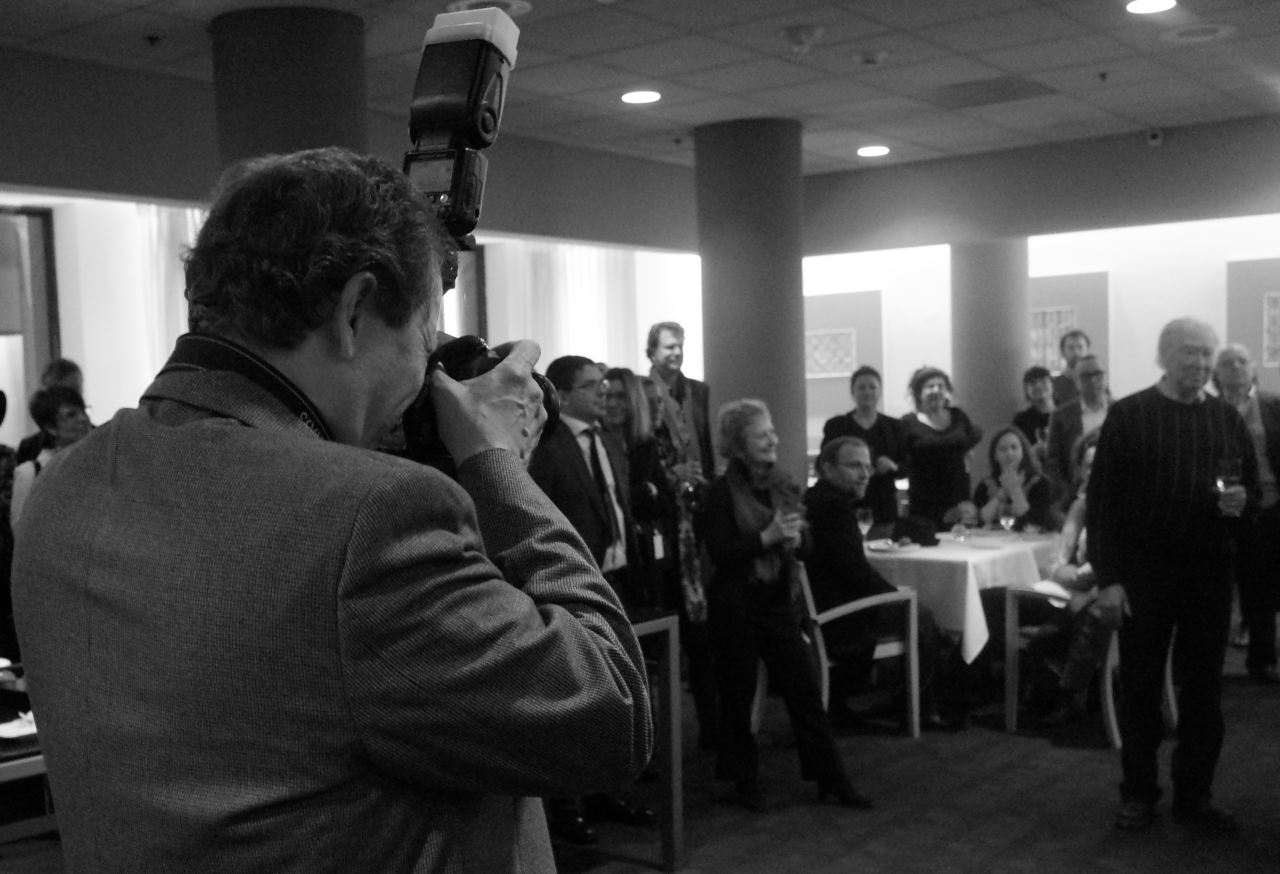 A photograph of the photographer taking a photograph of Michael Snow at the opening of a show of Michael Snow's photographs. Philadelphia Museum of Art Jan. 30, 2014