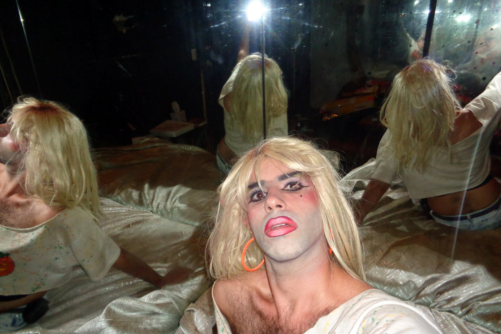 "A selfie taken backstage at the former venue, The Spectrum. ""I like the depiction of fractured selves in the dirty mirror, the glow of the point-and-shoot flash, and my heavy liner/gradient lip look."""