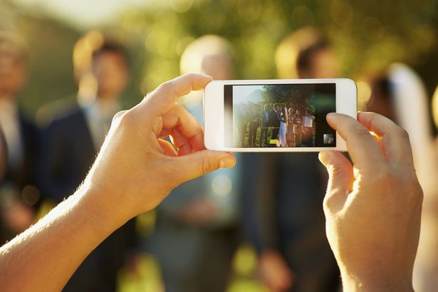 Taking-a-picture-of-a-wedding-on-mobile-phone.jpg