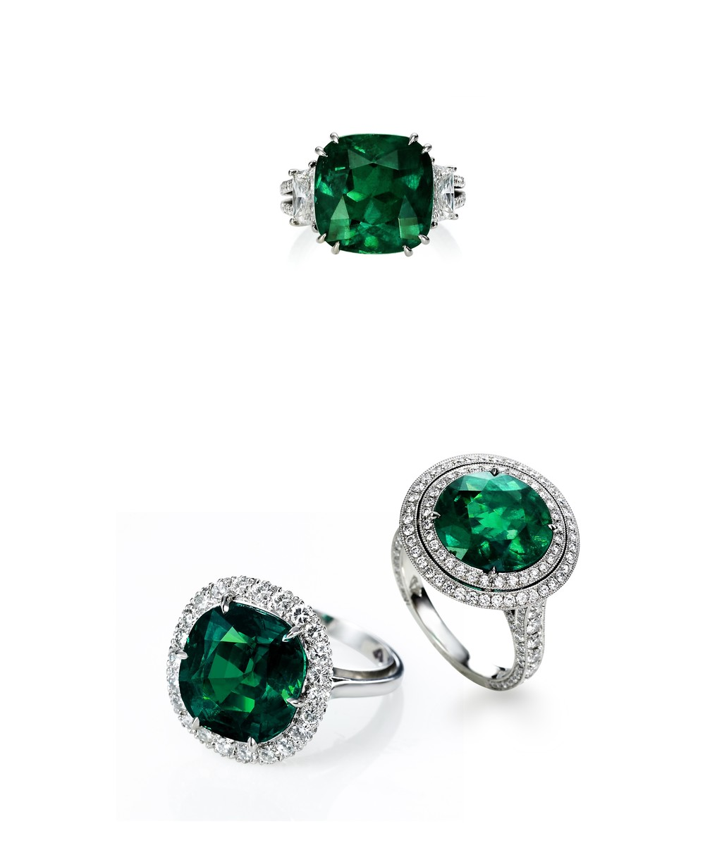 "Emerald & Diamond Rings    From left to right:    Cushion Cut, ""Gem"" Colombian Emerald and Diamond Ring, AGL Certificate   Cushion Cut, ""Super-Gem"" Colombian Emerald and Diamond Ring, AGL Certificate   Custom Made, Round, ""Gem"" Colombian Emerald and Diamond Ring, AGL Certificate"
