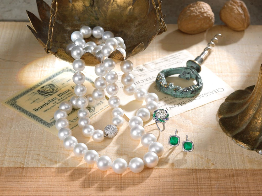 White South Sea pearl necklace. Signature diamond and sugerloaf cut emerald earrings. Emerald, sapphire and diamond ring.