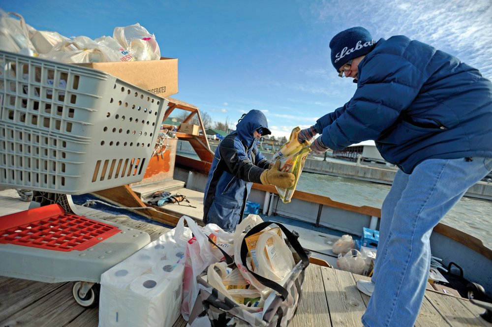 "AMANDA MORRISON / NNY LIVING Eileen ""Urch"" Balcom-Slate, right, hands a bag of dog food to her husband, Harry, as they load up their boat with a month's worth of provisions before heading home to Grindstone Island."