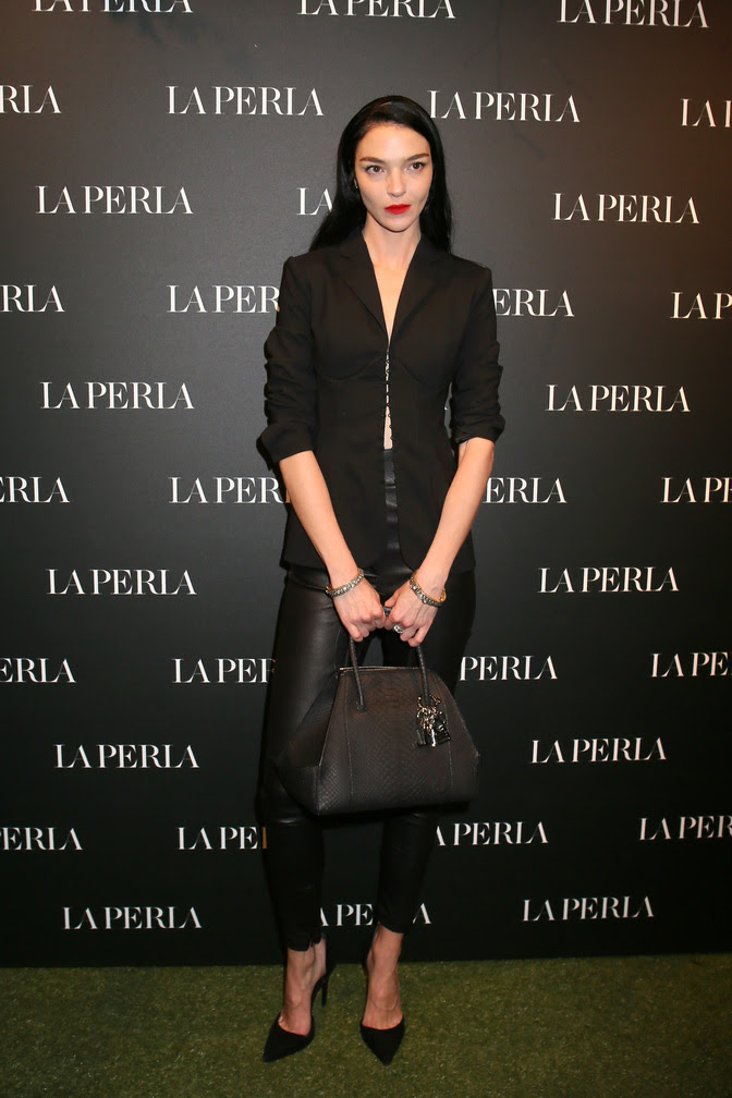 "MariaCarla Boscono wearing the La Perla SS17 Corset Jacket in Black with SS17 rubberized python ""Ada"" bag with La Perla charm in silver and black enamel."
