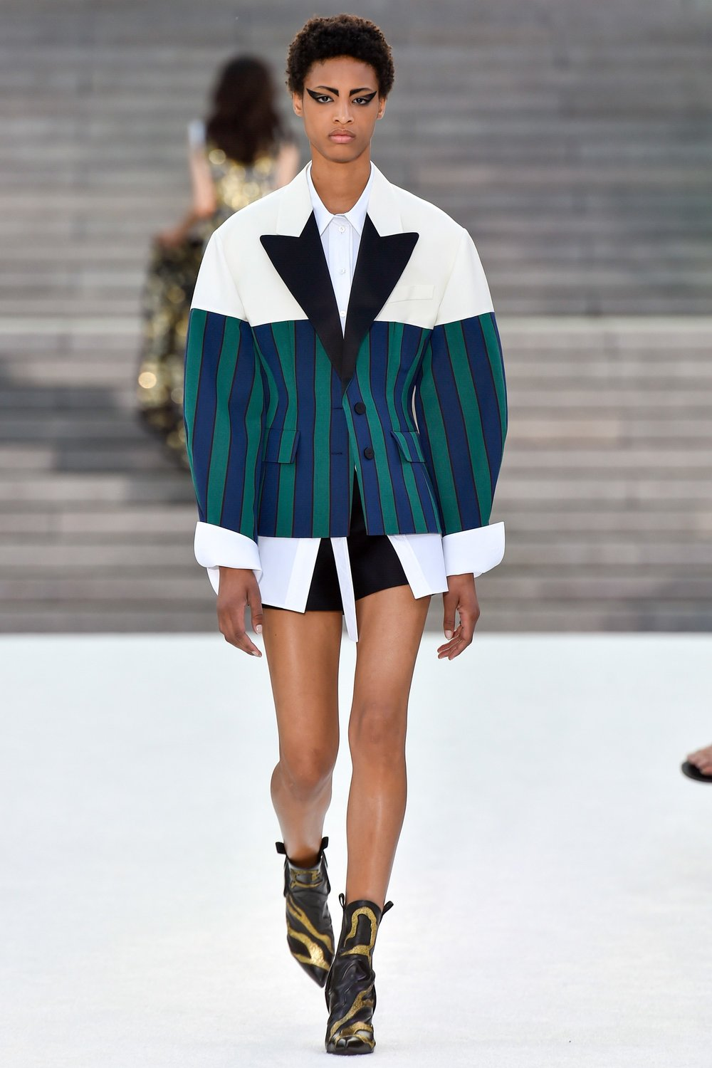 Since the old days at Balenciaga, Nicolas Ghesquière's tailoring has been influential. It commanded most of the attention here. He indicated that the oversized, yet hourglass blazers near the end of the show were inspired by traditional Japanese styles, while the rounded, standout shoulder lines on a series of short-sleeved jackets seemed to nod backwards at a collection he did in the late aughts. But mostly he preferred a boyish, cropped style with a hem that barely grazed the hips and shortened sleeves. -Vogue -