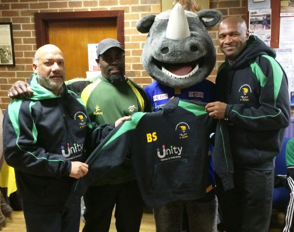 Unity Homes and Enterprise chief executive Ali Akbor (left) and director of regeneration Wayne Noteman (right) present Chapeltown Cougars head coach Steve Walker with a new hoodie, watched by Ronnie the Rhino