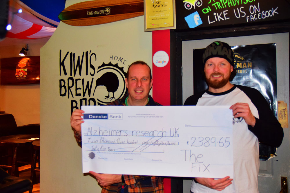 Job done: Jonny Lennox (left), frontman of The Fix, and Kris Charteris, owner of Kiwi's Brew Bar, display a cheque for Alzheimer's Research UK following the band's 25-year charity reunion night