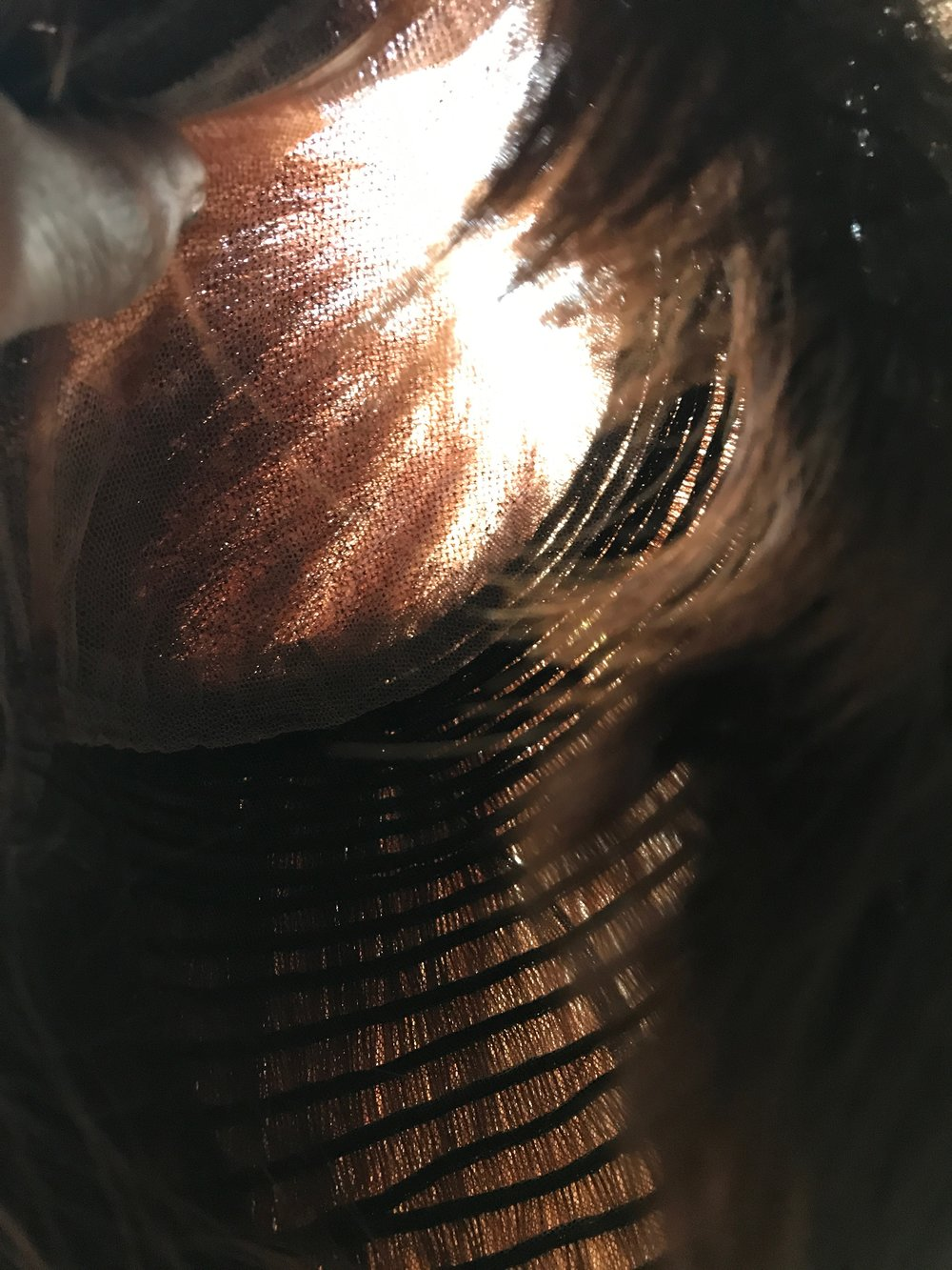 The interior of a 3-year old Follea full wig. The lace front at the top and even the wefting on the bottom (which is different then than Follea wigs are now) show that you can see daylight through the hair fibers.  Daylight=cooler wig wearing.