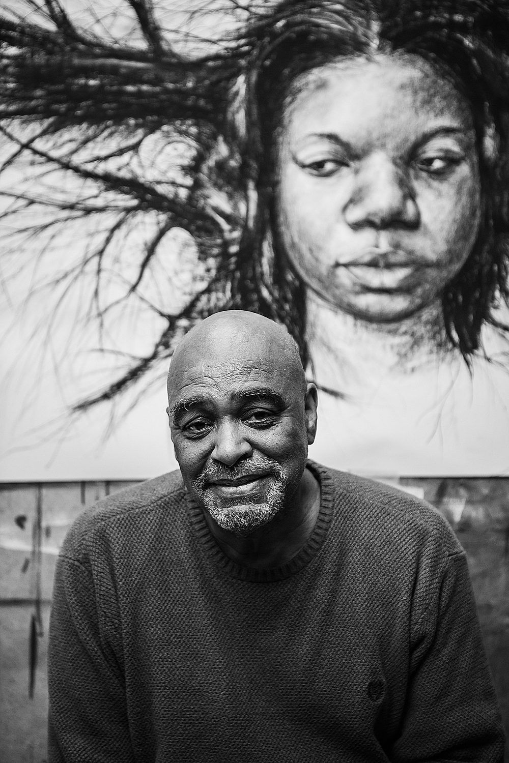 black and white photo of man in front of mural