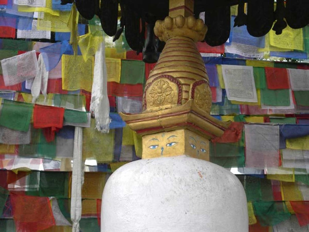 A rich tapestry of prayer flags provide the backdrop for a small Buddhist Gompa at the Swayambhu Temple, Kathmandu