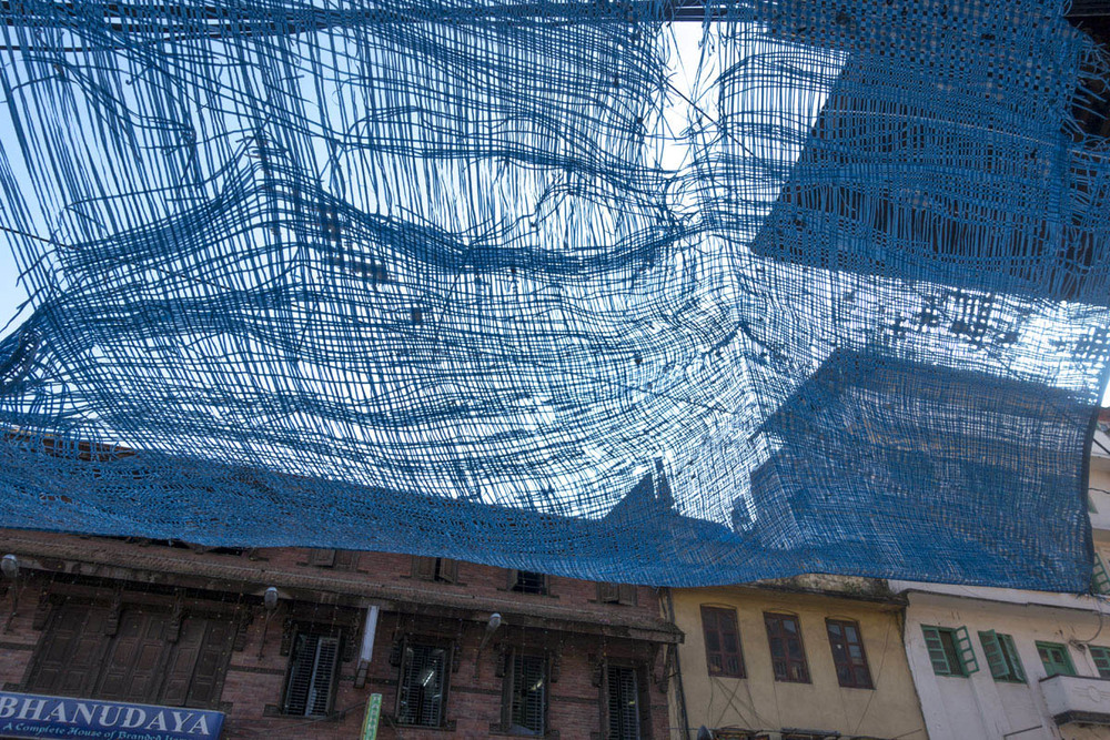 A weather worn tarp provides an element of color against the backdrop of  Durbar Square, in Kathmandu