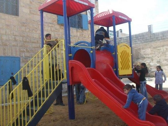 Palestinian children enjoying their new playstructure.